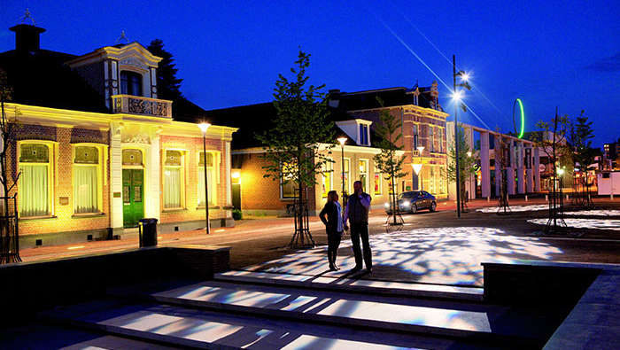 Man and woman are walking in a square beautified with Philips lighting
