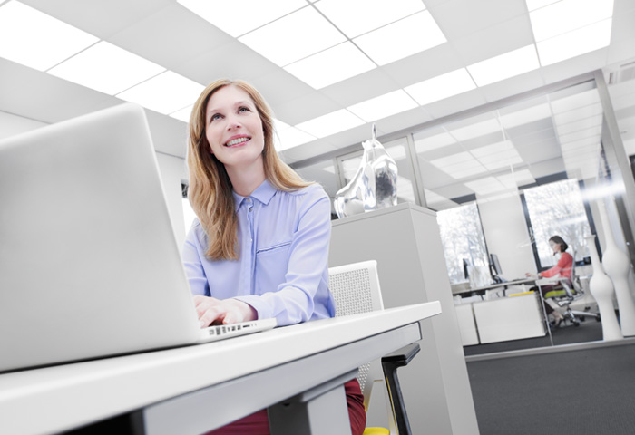 Woman in an office with Soundlight Comfort ceiling